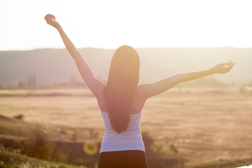 cheering woman open arms to sunrise